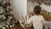 камин : Little boy putting logs into Christmas decorated fireplace Стоковые видеозаписи