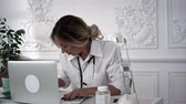 pediatrics : Female doctor sitting at worktable and writing prescription on special form. Stock Footage