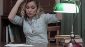 победитель : Pretty young woman sitting at her desk with books and having funny little dance Стоковые видеозаписи