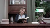 compromisso : Pretty young female sitting at her desk and researching information in the book for business report Vídeos