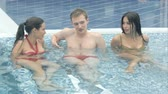 tub : Young people enjoying the hot tub in the swimming pool