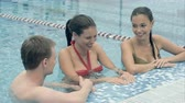 pool deck : Two beautiful women talking to a young man in the swimming pool