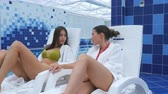 köntös : Happy female friends dressed in bathrobes and bikini relaxing at spa next to a swimming pool Stock mozgókép