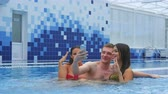 kozmopolita : Two beautiful women and a young man taking selfies in the swimming pool