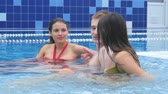 fürdőkád : Two beautiful women and a young man talking and relaxing in jacuzzi in the pool