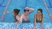 três pessoas : Two happy young women and a young man having fun in the swimming pool