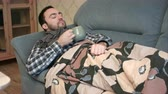 doku : Sick young man drinking hot tea or anti-fever medicine in bed Stok Video