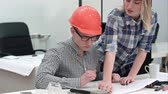 divider : Architect working on blueprints while female colleague bringing more drawings