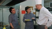 kitchenware : Young male cooks trying shrimp salad cooked by chef and discussing it
