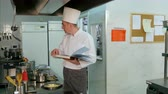 původní : Head chef looking for recipe in a cookbook while checking upon his trainee Dostupné videozáznamy