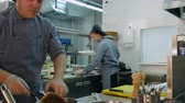 chef uniform : Three busy male cooks working in the restaurant kitchen