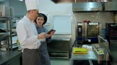internovat : Chef explaining something to cook trainee in hat using digital tablet