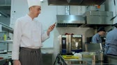 mobile kitchen : Head cook standing in the kitchen and using his cell phone Stock Footage