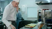 chef uniform : Chef talking on the phone and tossing ingredients on a frying pan in the restaurant kitchen Stock Footage