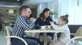 four children : Happy young parents chatting witn daughter during their family vacation in cafe drinking tea. Stock Footage