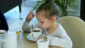 lampart : Little russian girl holding spoon and stiring sugar in tea at restaurant. Wideo