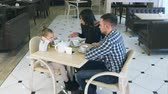 угрюмый : Indignant mother blaming on daughter and husband in cafe. Littke girl closing her ears. Стоковые видеозаписи