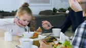 squash family : Family have healthy lunch at restaurant. Little daughter eating vegetable salad with white bread. Stock Footage