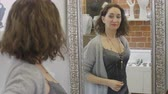 necklace : Elegant woman putting necklace on her neck in front of mirror in store Stock Footage