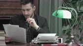 şair : Young journalist reading printed articles sitting at the desk with typewriter Stok Video