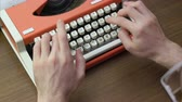 psaní na stroji : Mans hands typing on an old red mechanical typewriter