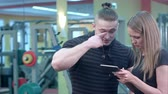rehberlik : Personal trainer using digital tablet while talking to woman at gym