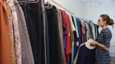 продавщица : Sales assistant in clothing store fixing wardrobe