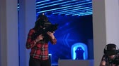 mounted : Young woman and man playing VR shooter game with virtual reality guns and vr glasses Stock Footage