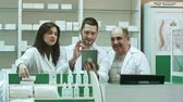 advise : Competent pharmacy team with pharmacist and pharmacy technicians having video chat with colleagues using digital tablet