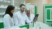 pharmaceutics : Team of pharmacist having video chat using digital tablet at pharmacy Stock Footage