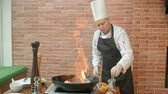 preparar : Chef preparing seafood in pan with alcohol in big flame