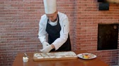 flatten : Chef cut out circles from raw cookie dough rolled seam on a wooden board Stock Footage