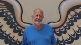 kirli : Old man standing in front of wings wall graffiti