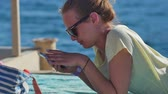 лежа : Young woman in sunglasses lying with smartphone on a beach