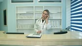 traumatology : Busy young nurse using tablet and phone at reception desk