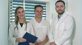 expressando positividade : Two male doctors and female doctor with stethoscope smiling to the camera