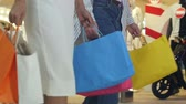 posh : Low shot of two girls that are walking through a clothing store in colorful garments