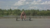 Sporty woman exercising with barbell over city waterside background Vídeos
