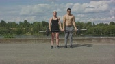 Young happy sports couple working out with barbell together