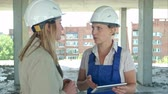 partnership : Female engineer and worker on construction site with plan on digital tablet
