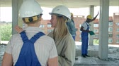 supervising : Young architecture and female worker talking at open air construction site