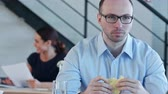 board : Young business man sitting and eating sandwich with cheese in office