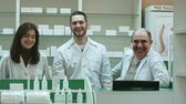 verkoopster : Three competent pharmacists laughing in a pharmacy looking at camera Stockvideo