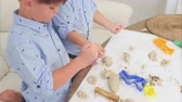 utensili da cucina : Two cute little boys playing with dough and learning how to bake