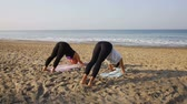 sea : Teacher and student doing yoga at Sunrise