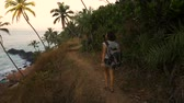 compromisso : Cheering young woman backpacker at sunrise seaside mountain peak