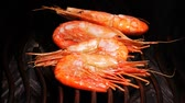 cooks : Slow motion shot of delicious shrimps on the grill