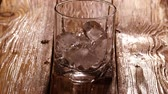 icecubes : Tilt up 1080p shot of whiskey or bourbon pouring into the glass