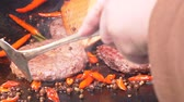 жарить : Slow motion shot of the delicious premium beef burgers are being fried with hot red peppers