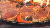pimentão : UHD closeup shot of the delicious lamb chops frying with vegetables and herbs